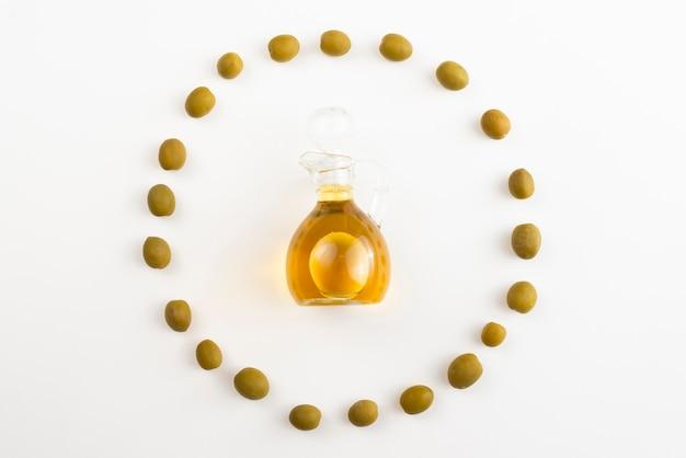Olives circle shape surrounding olive oil bottle Free Photo