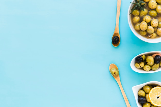 Olives in different bowls and two wooden spoon over the blue background Free Photo