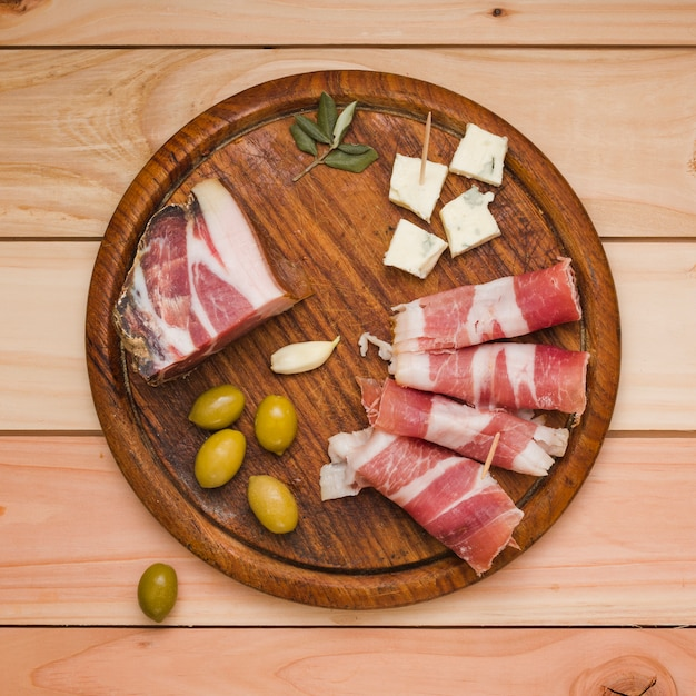 Olives; garlic clove; cheese slice and bacon on wooden tray over the desk Free Photo