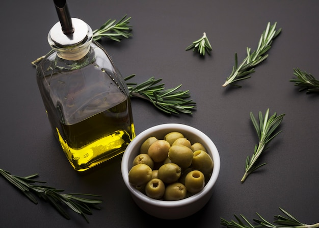 Olives and olive oil and rosemary on black slate surface Free Photo