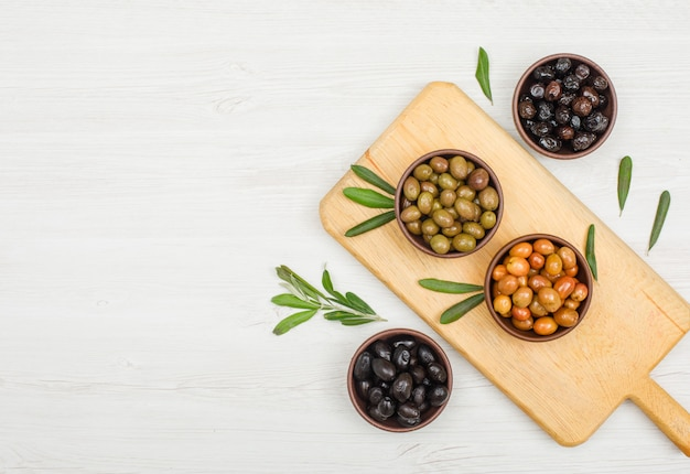 Olives variety with olive tree leaves in a clay bowls and cutting board on white wood, flat lay. Free Photo