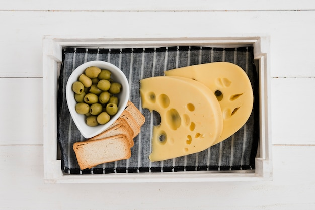 Olives with toast bread and maasdam cheese on napkin in tray over the wooden desk Free Photo