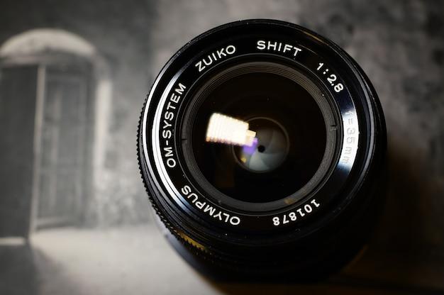 Obiettivo olympus om shift 35mm f2.8 su un libro fotografico Foto Gratuite