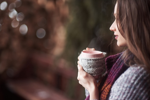 Oman wearing warm knit clothes drinking cup of hot tea or coffee outdoors Premium Photo