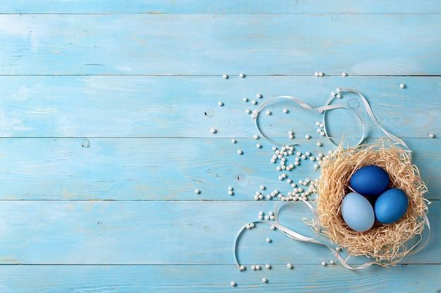 Пасхальная концепция. яйца ombre в голубых цветах на голубой деревянной предпосылке с космосом экземпляра для текста. вид сверху вниз или плоская планировка. классические синие цвета на пасху 2020 Premium Фотографии