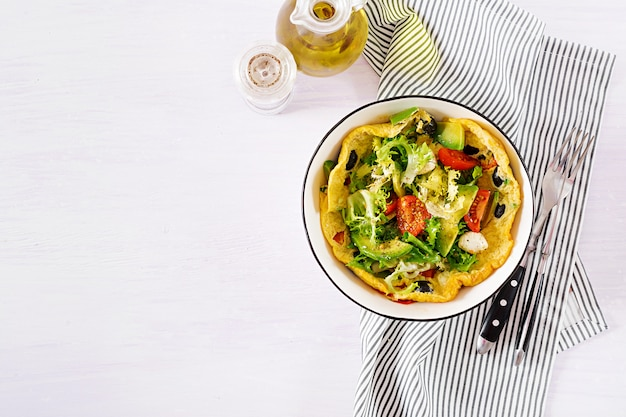 Omelet with fresh tomatoes, black olive, avocado and mozzarella cheese. Premium Photo