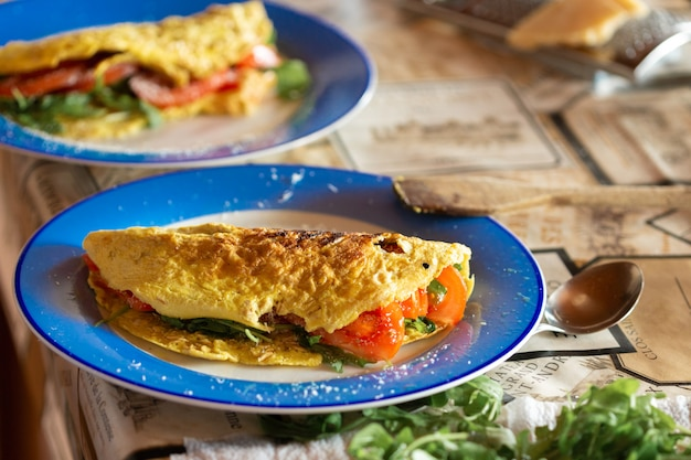 Omelet with tomatoes and arugula Premium Photo