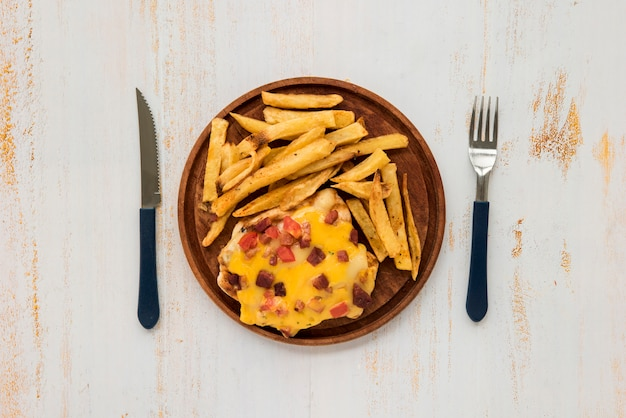 Omelette and french fries on wooden board on grunge painted desk Free Photo