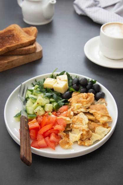 Омлет со свежими овощами: руккола, помидоры, огурцы, оливки, сыр. темный стол. вид сверху. Premium Фотографии