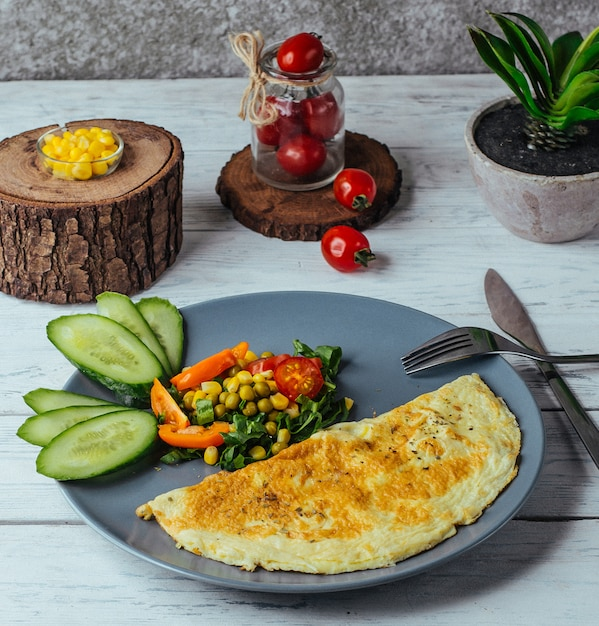 Omelette with salad of cucumber, tomato,corn and herbs in rustic style Free Photo