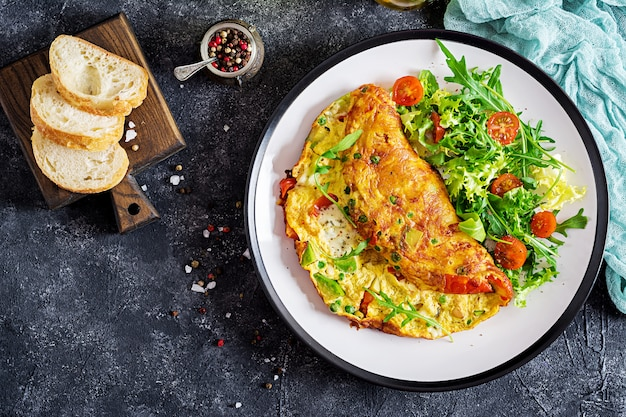 Omelette with tomatoes, avocado, blue cheese and green peas Premium Photo