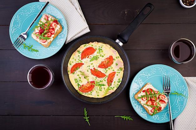 トマト、ハム、ネギ、暗いテーブルの上のイチゴのサンドイッチとオムレツ。フリッタータ-イタリアのオムレツ。上面図 Premium写真