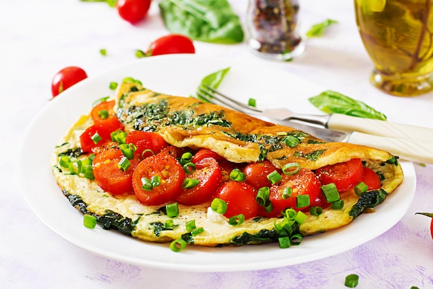 Omelette with tomatoes, spinach and green onion on white plate. Premium Photo