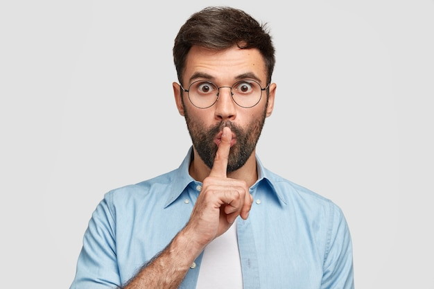 Omg, be silent! puzzled young male touches lips with index finger, stares, makes hush gesture, afraids someone will tell his secret, has thick bristle, isolated over white wall Free Photo