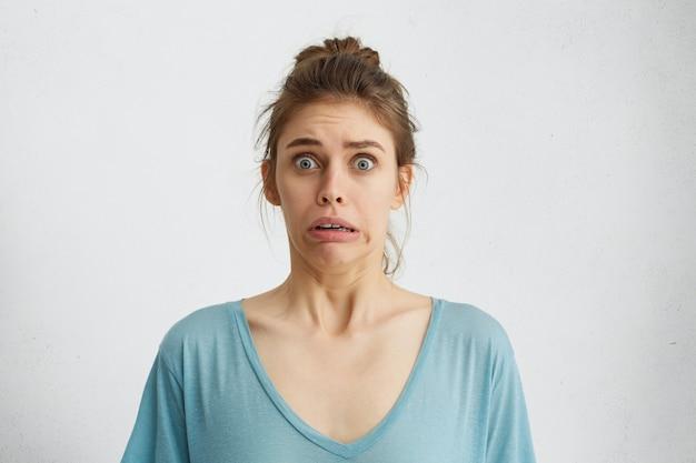 Oh mio dio! spaventata, terrorizzata, donna con gli occhi azzurri spuntati fuori aggrottando le sopracciglia con il panico. Foto Gratuite