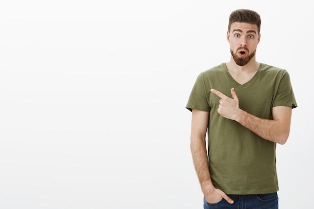 ええ、それは本当です、チェックしてください。驚くべき言葉のないハンサムなあごひげを生やした男の肖像が驚くべき製品から顎を落とし、信じられないほどの製品を見て、口を開け、興奮して左を指すように目を広げた 無料写真