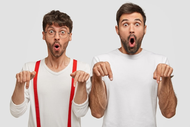 Omg, its impressive. horizontal shot of thrilled astonished two young men gasp from astonishment, point with both index fingers on floor, being blessed with idea, isolated over white wall Free Photo