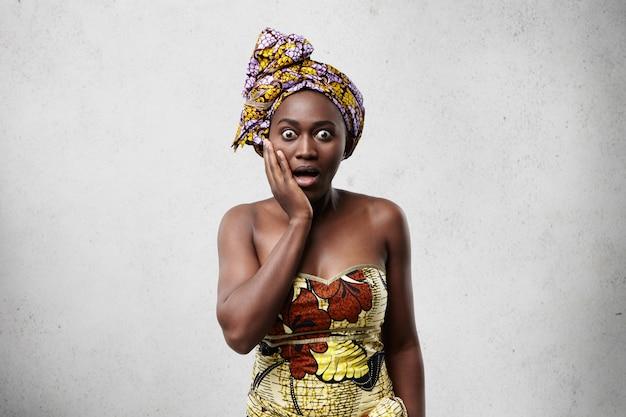 ああ、神様!驚きや恐怖のアフリカの女性が頬に手を握ってショックを受け、目を飛び出させ、口を大きく開いたままにしている 無料写真