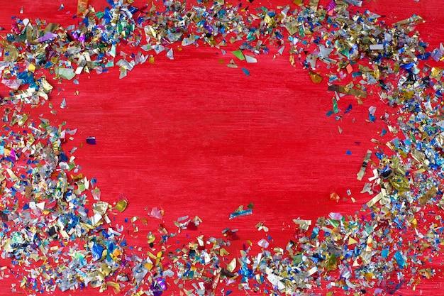 На красном фоне конфетти разбросаны по кругу и посередине Premium Фотографии
