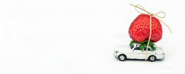 На белом фоне маленькая игрушечная машинка с красной клубникой место надписи. Premium Фотографии