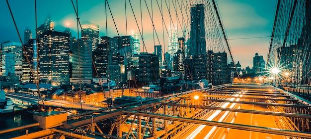 夜のブルックリン橋で車の交通、ニューヨーク。 Premium写真