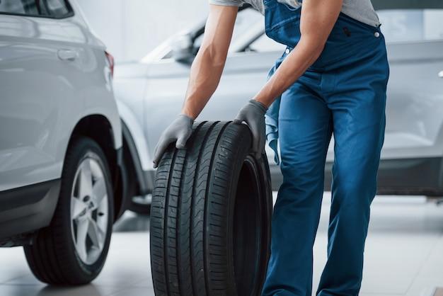 行く途中です。修理ガレージでタイヤを保持しているメカニック。冬用および夏用タイヤの交換 無料写真
