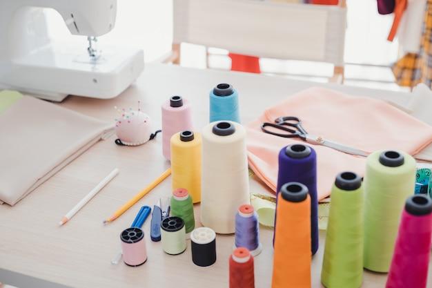 На столе дизайнера есть много аксессуаров, используемых для шитья. Premium Фотографии