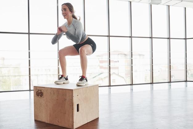 На краю коробки. спортивная молодая женщина имеет фитнес-день в тренажерном зале в утреннее время Бесплатные Фотографии