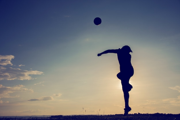 One asian soccer football player young man heading in silhouette Premium Photo