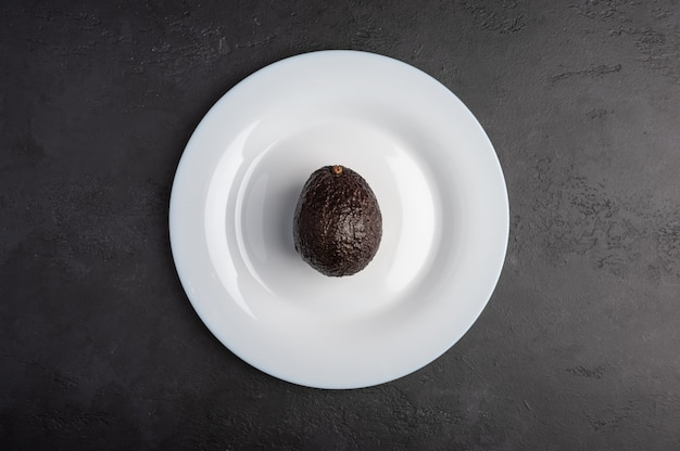 One avocado in the peel served in white plate on moody black background. top view, healthy diet concept, copy space Premium Photo