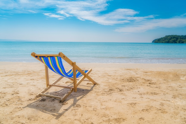 One beach chairs on the white sand with blue sky and summer sea Premium Photo