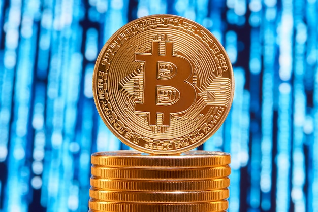 One bitcoin on edge placed on stack of golden bitcoins with blurred blue circuit on background. Premium Photo