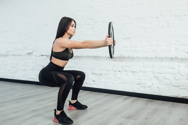 Один, женщина брюнет кавказская работая упражнения бодибилдинга фитнеса в студии. скопируйте пространство. Premium Фотографии