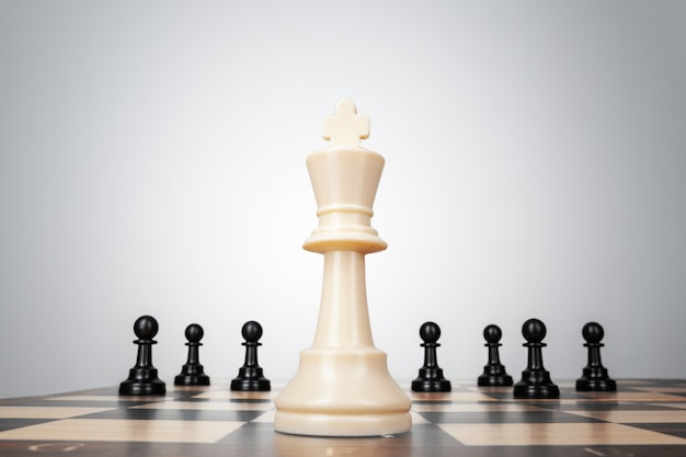 One chess pieces staying against thel set of chess pieces. strategy, business concept Premium Photo