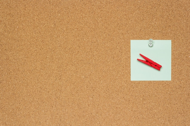 One colorful notes with white pushpins and clothespins isolated on a cork background Premium Photo