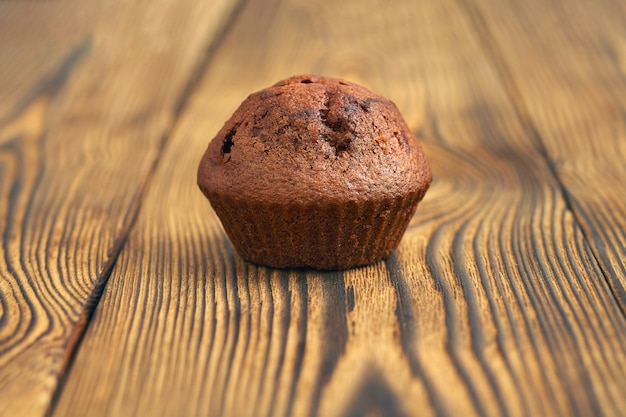 One dark chocolate dough muffin on the background of an old wooden table. Premium Photo