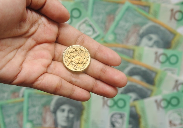 One dollar australia golden coin on hand on one hundred banknote background Premium Photo