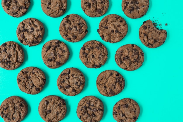 One eaten cookie among the fresh baked cookies on turquoise background Free Photo