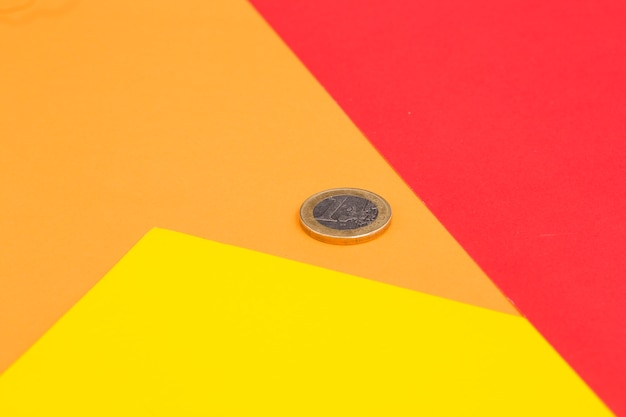 An one euro coin on red; yellow and orange colored background Free Photo