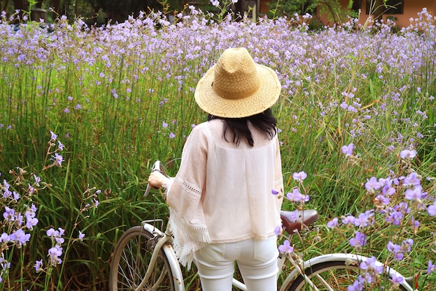 One female with her bicycle admiring the beautiful pastel purple flower field Premium Photo