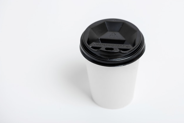 One focused take away white paper cup with black cap presented in front, isolated on simple gray background Premium Photo