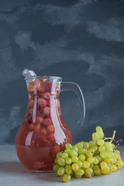 暗い背景にジュースのボトルとブドウの1つの新鮮な枝 無料写真