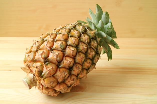 One fresh ripe pineapple whole fruit isolate on wooden background Premium Photo