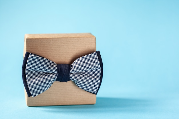 One gift box wrapped in craft paper and tied with the bow tie on blue background. concept father's day. Premium Photo