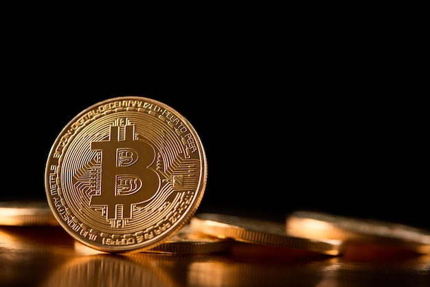 One golden bitcoin on its edge shown on the background of other cryptocurrencies introducing future trend of virtual money. Premium Photo