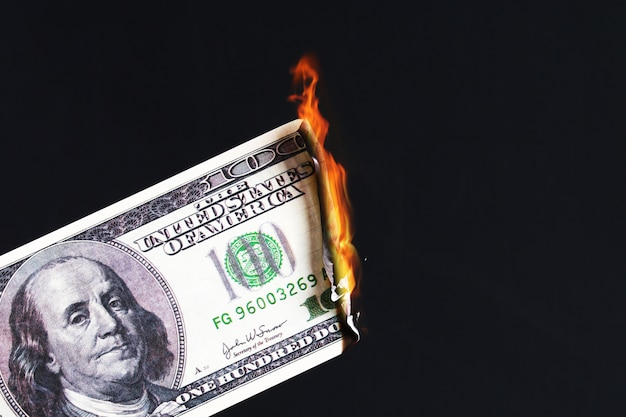 One hundred american dollar burning in fire flame. collapse of dollar. devaluation. falling currency Premium Photo