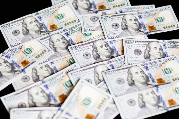 One hundred dollar bills on black Premium Photo