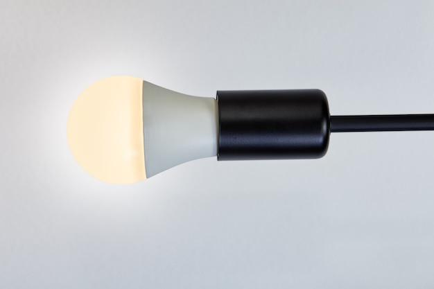 2700 켈빈의 따뜻한 색온도를 가진 Led 전구 1 개, 흰색 천장에 전기 램프가있는 램프 홀더. 프리미엄 사진