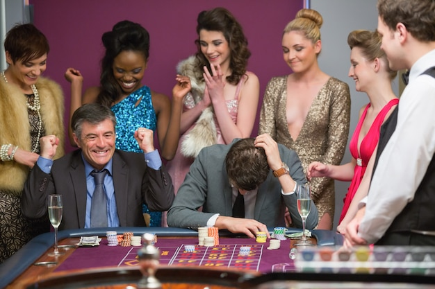 One man winning and one man losing at roulette table Premium Photo