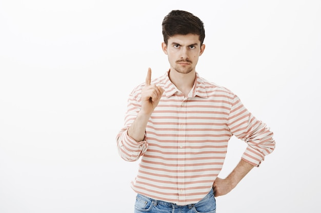 One more thing. indoor shot of displeased angry european man with moustache  and beard, shaking index finger and frowning from displeasure and annoyance  | Free Photo
